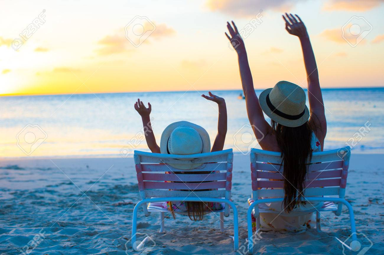 Little Girl And Happy Mother Sitting On Beach Chairs At Sunset