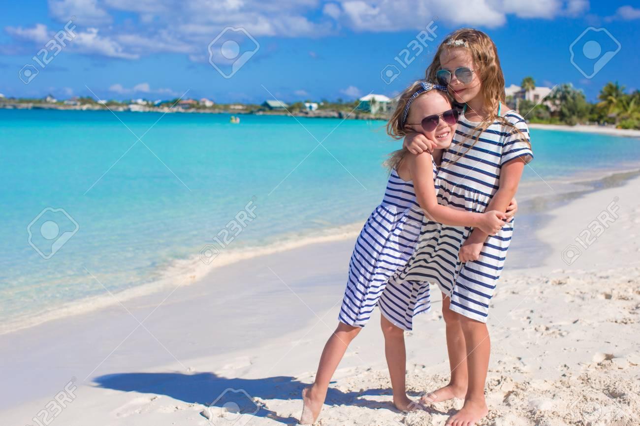 Little cute girls enjoy their summer vacation on beach Stock Photo - 28410186