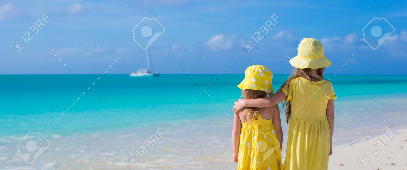 Back view of two sisters looking at the sea on the white beach Stock Photo - 30122909
