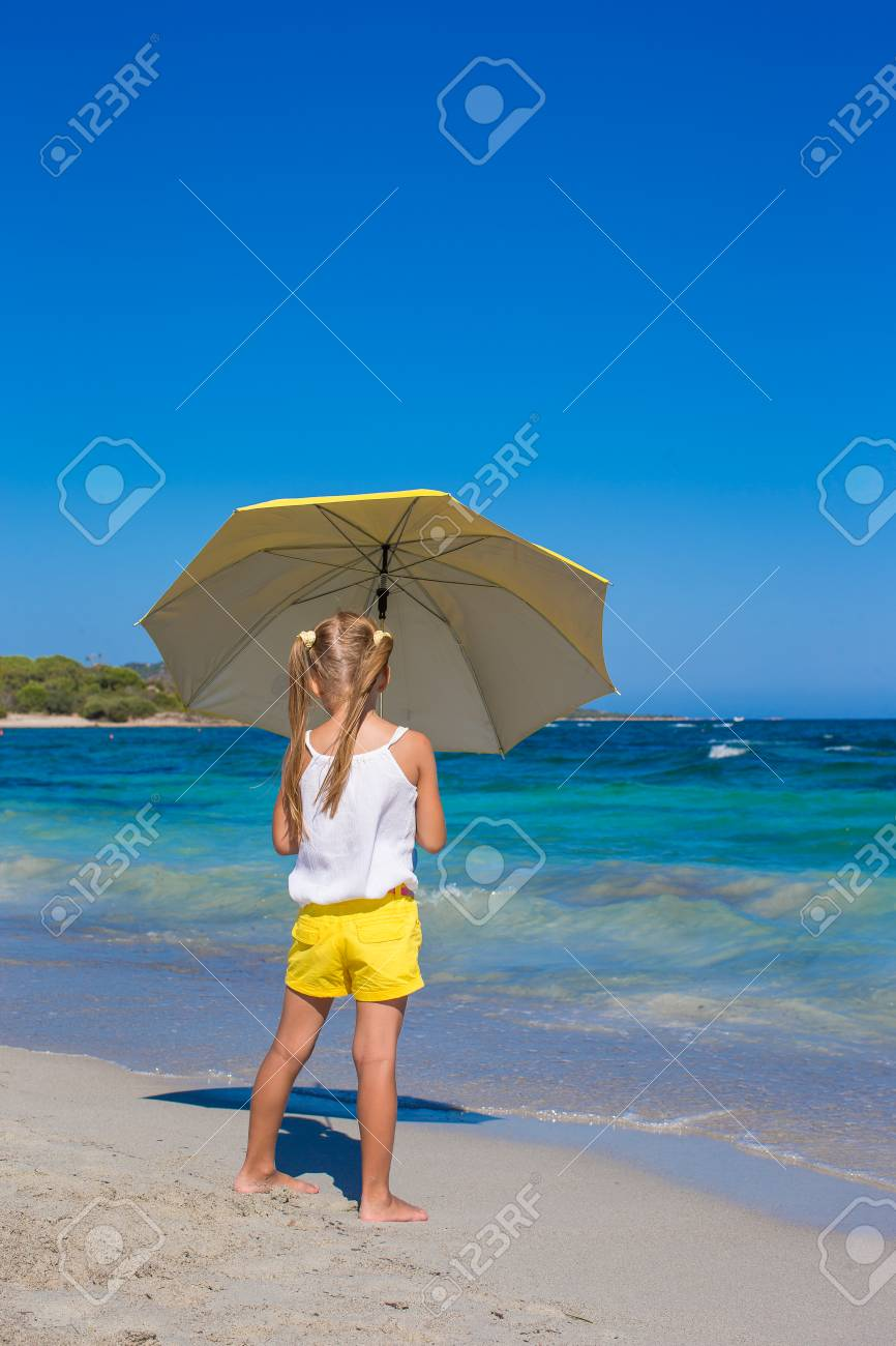 3ec310b9d1f25 Little cute girl with big yellow umbrella walking on tropical beach Stock  Photo - 31834335