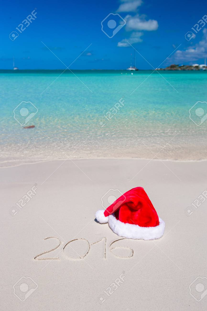 merry christmas written on tropical beach white sand with red xmas hat stock photo 32649969 - Merry Christmas Beach Images