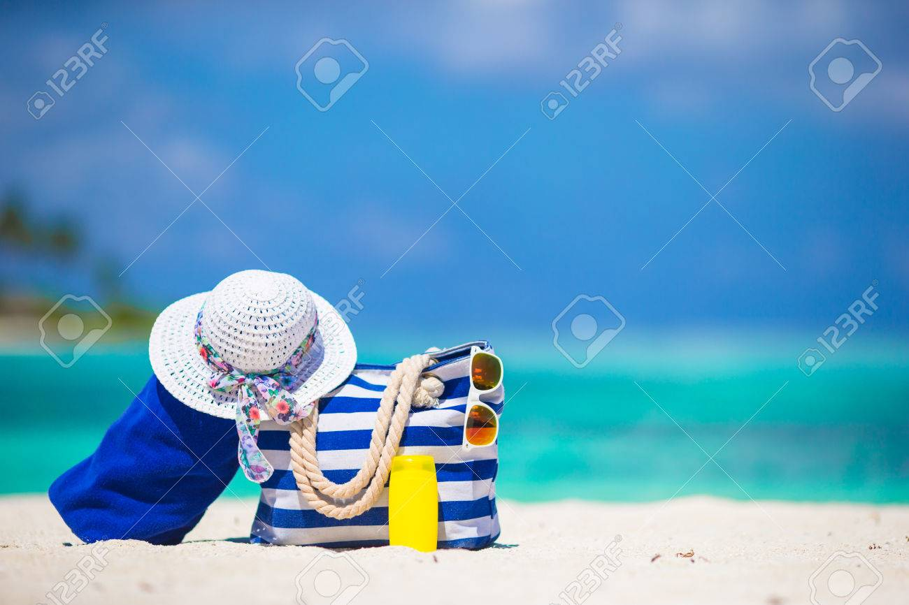 Blue stripe bag and towel, straw white hat, sunglasses, sunscreen bottle on exotic beach - 38983824