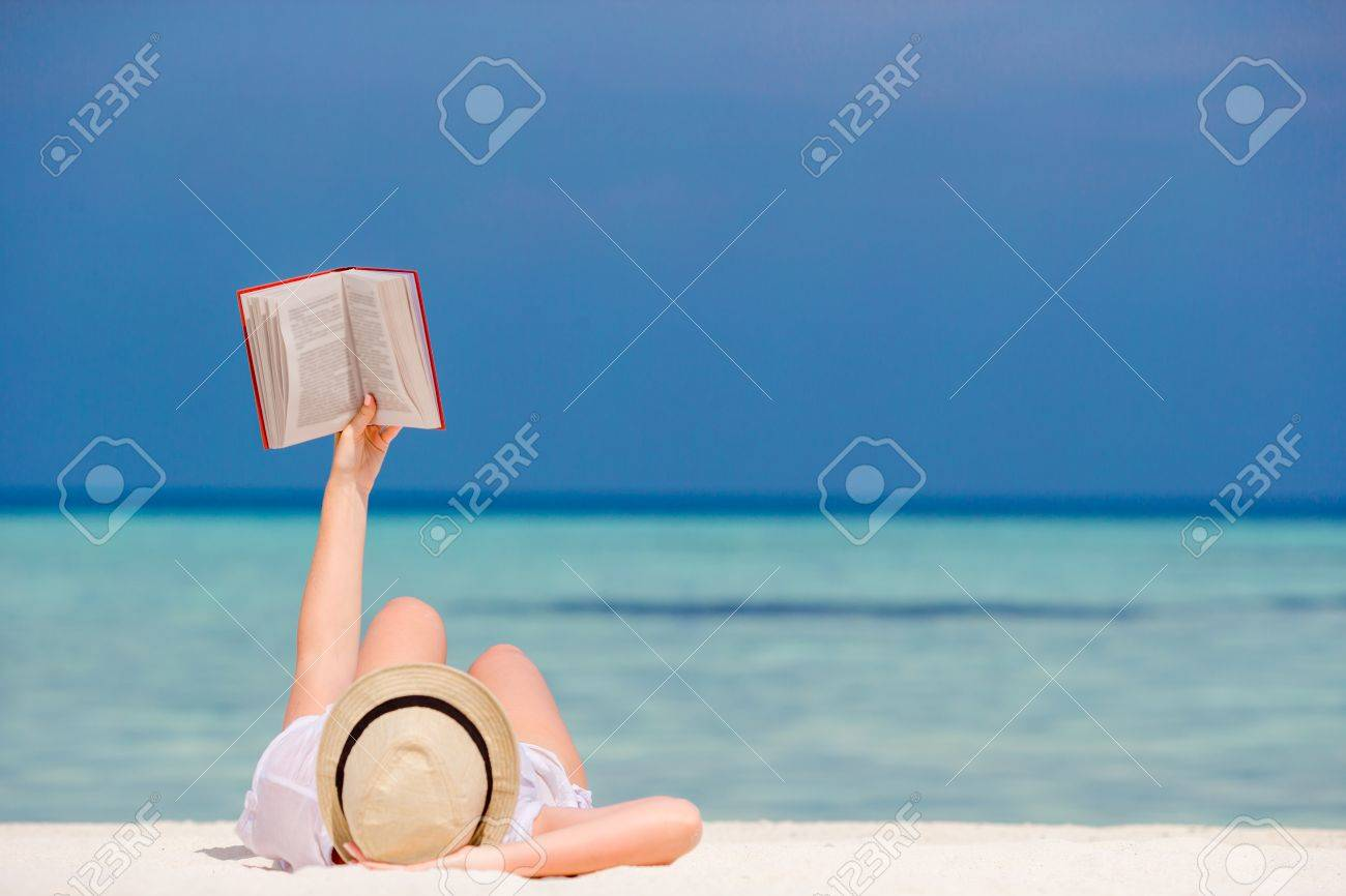 Young woman is reading a book lying on tropical white beach - 52542801