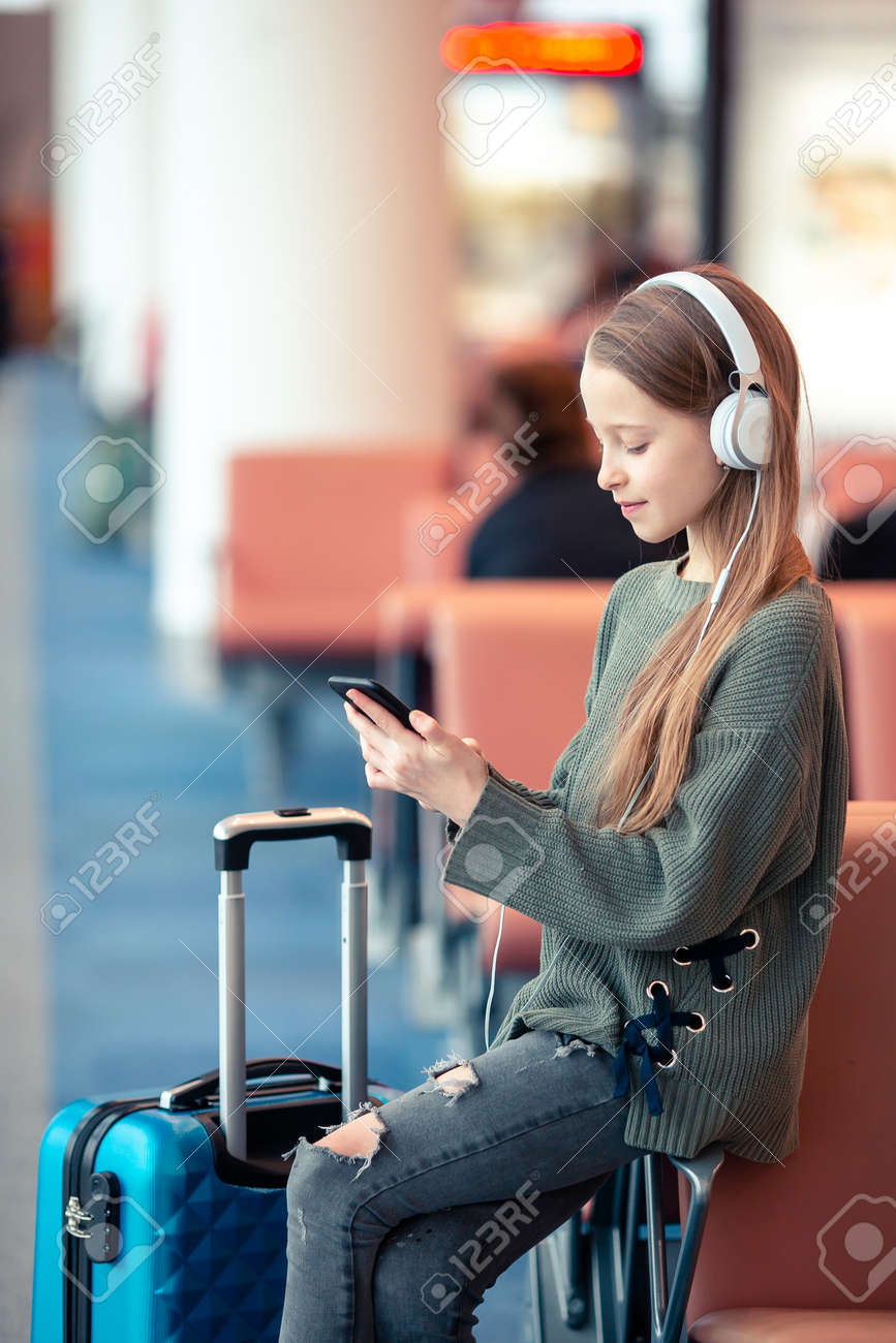 Adorable little girl at airport in big international airport near window - 121259282