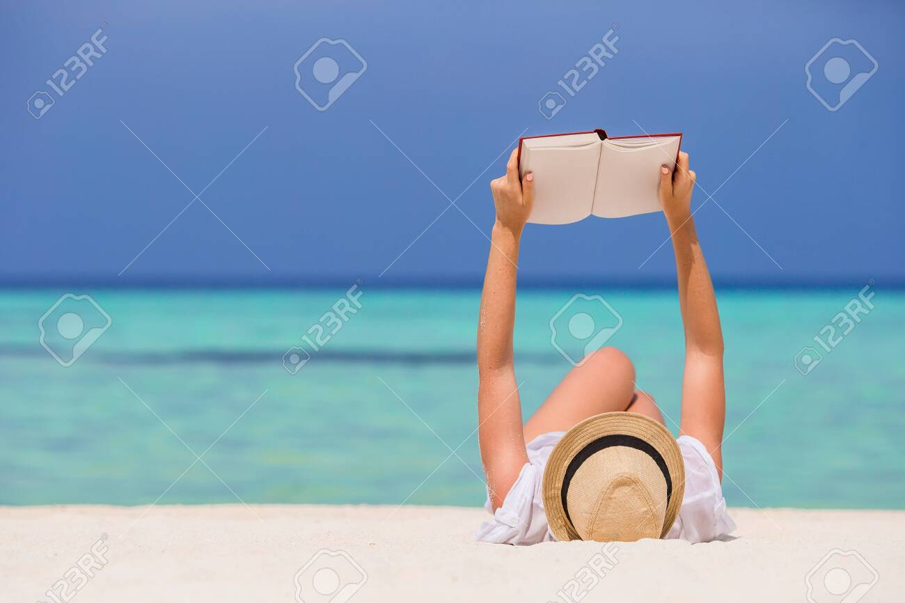 Portrait of a young woman relaxing on the beach, reading a book - 130125902