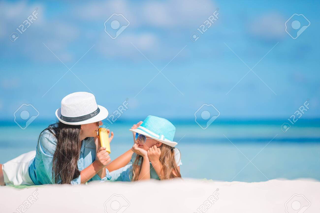 Mother applying sun cream to daughter hand. Sun protection - 136344253