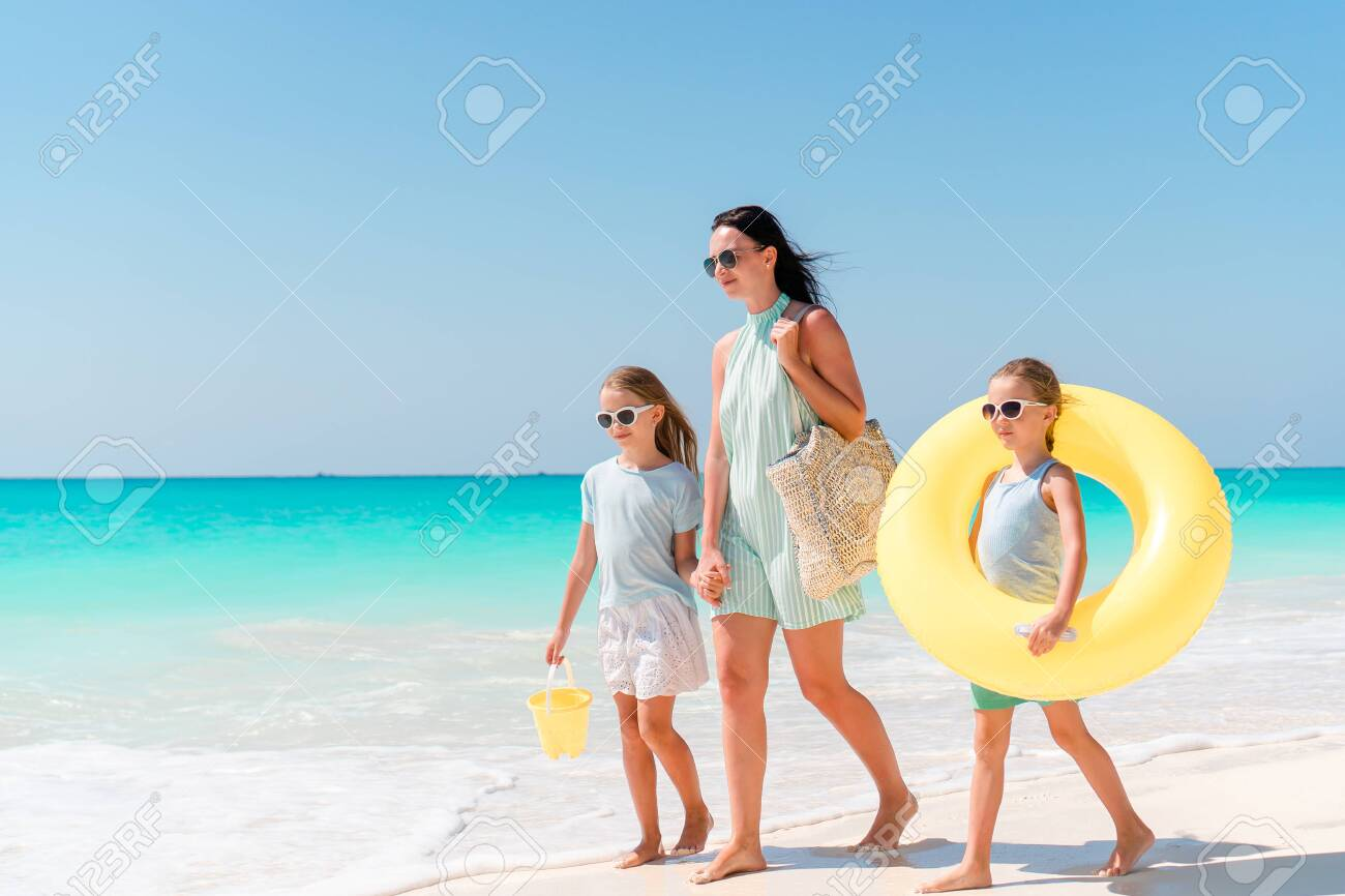 Adorable little girls and young mother on white beach. Family on the beach ready to swim - 143853510