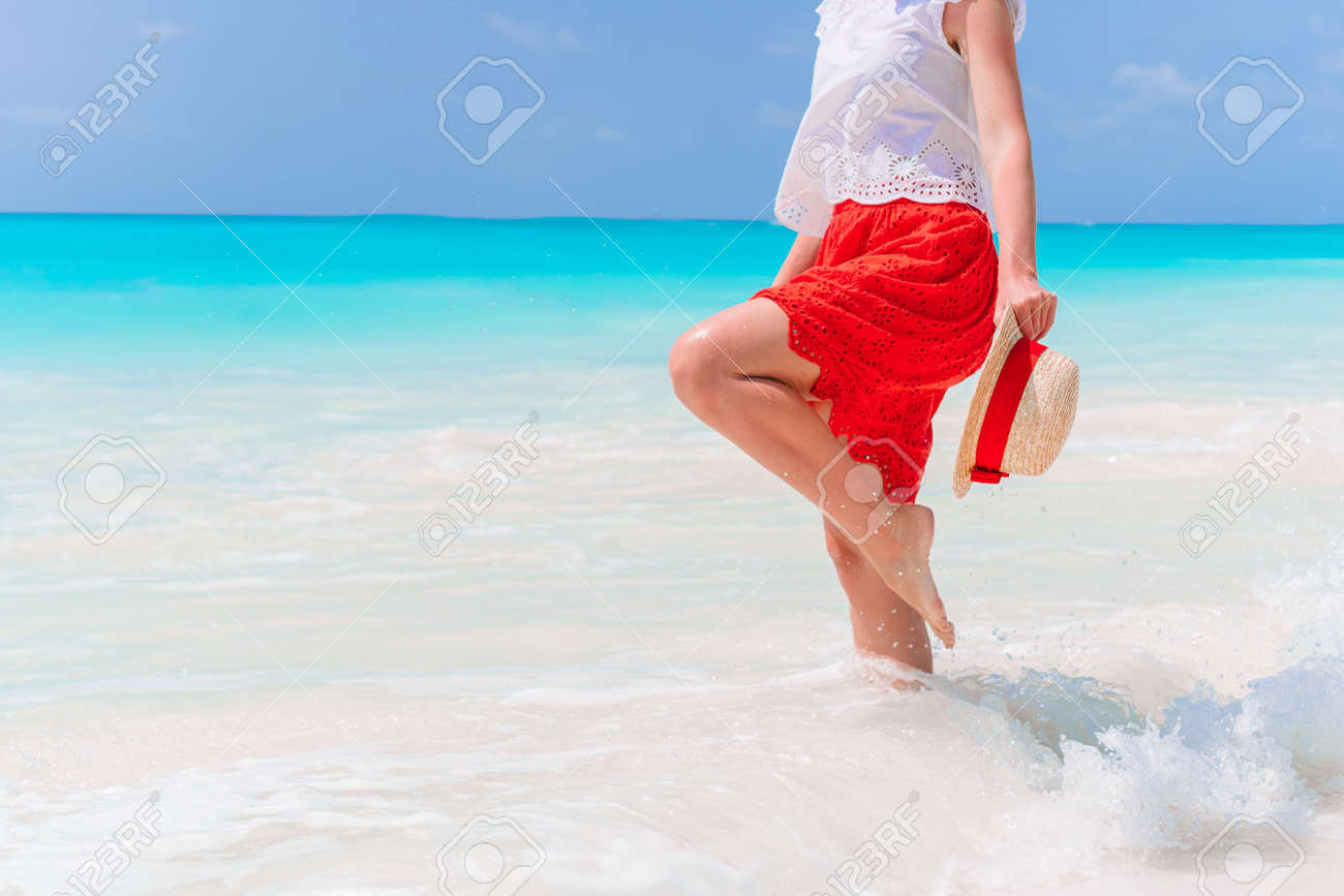Young woman enjoying the sun sunbathing by perfect turquoise ocean - 145319986