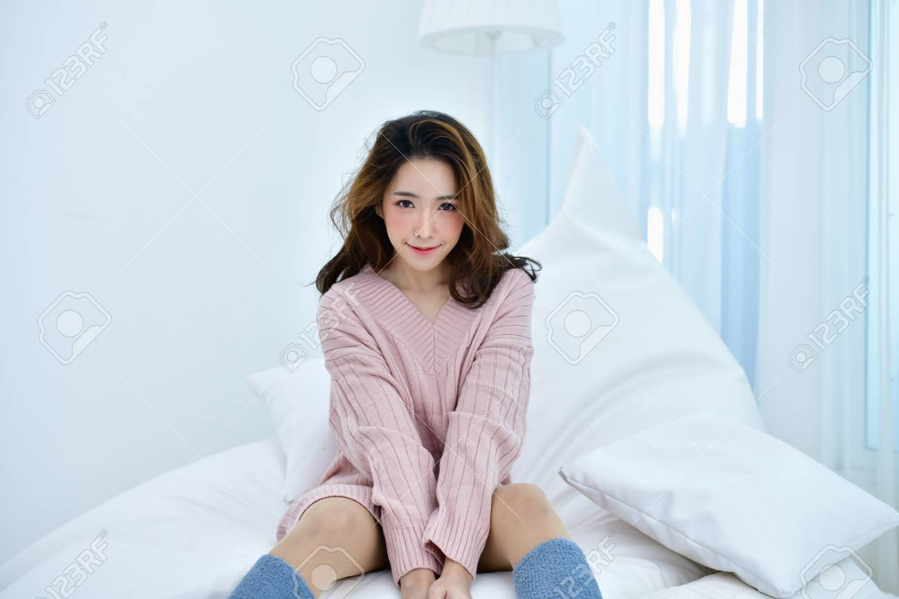 016a6908c Winter Concept. Cute Asian girl in winter dress. Beautiful woman is  relaxing in a white bedroom. Beautiful women in winter clothes are relaxing  in the ...