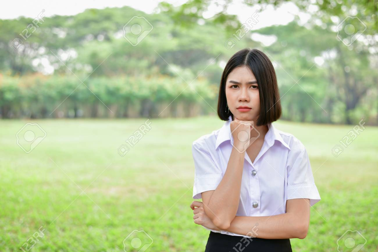 Education Concepts. Beautiful young Asian girl is thinking seriously. Beautiful Asian students are thinking in the garden. Beautiful young students are contemplating what they have learned. - 108952775