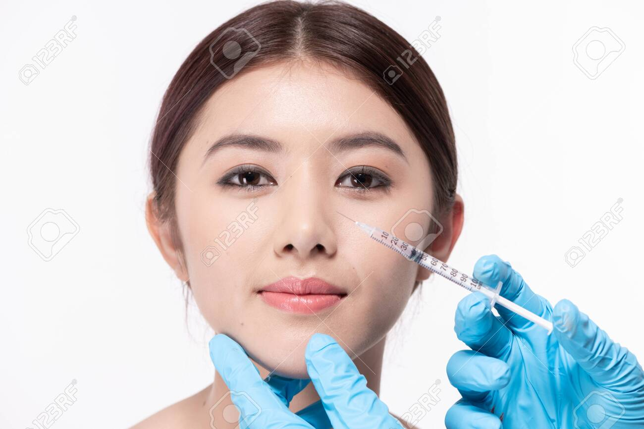 Surgery concept. The doctor cosmetologist makes the Rejuvenating facial injections procedure for tightening and smoothing wrinkles on the face skin of a beautiful. - 120474896