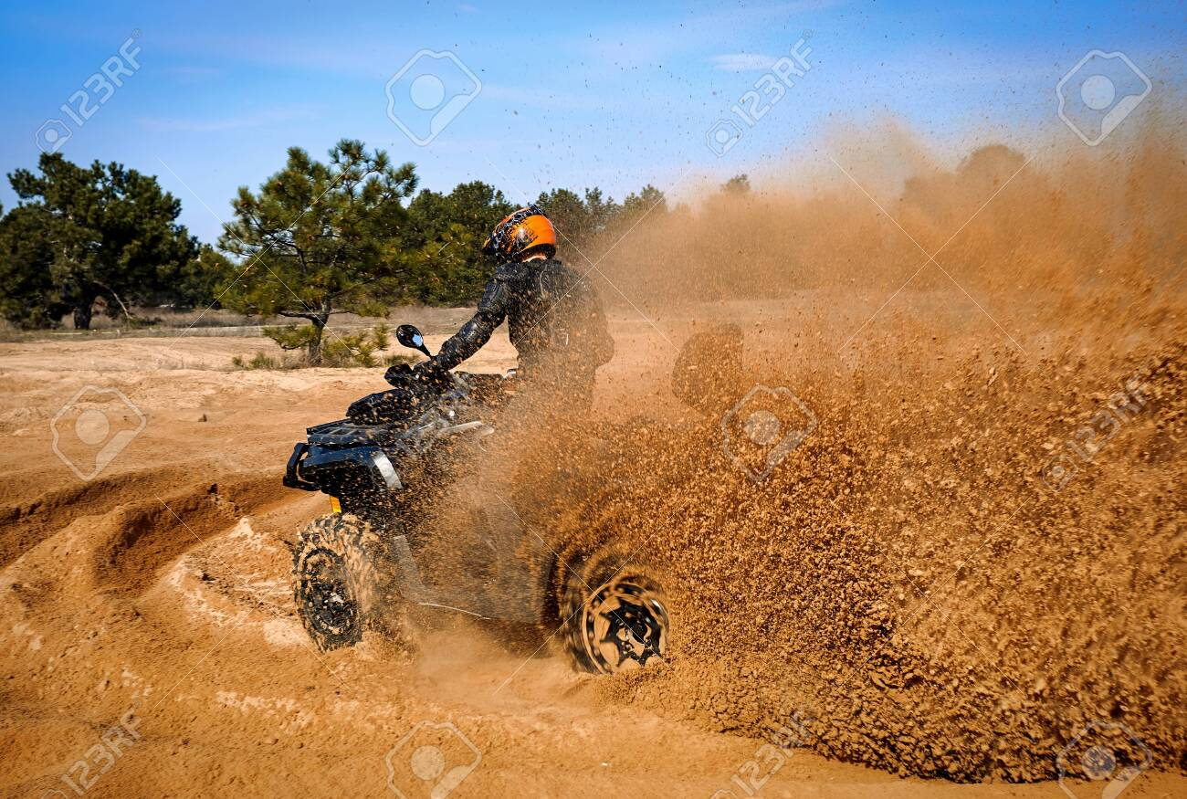 Racing powerful quad bike on the difficult sand in the summer. - 142668158