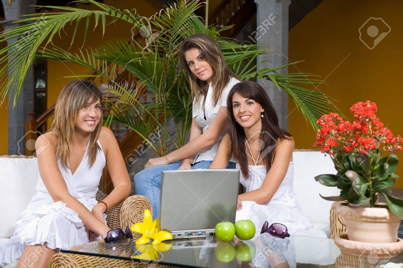 Three attractive young women working at a computer in a outdoor terrace Stock Photo - 1944377