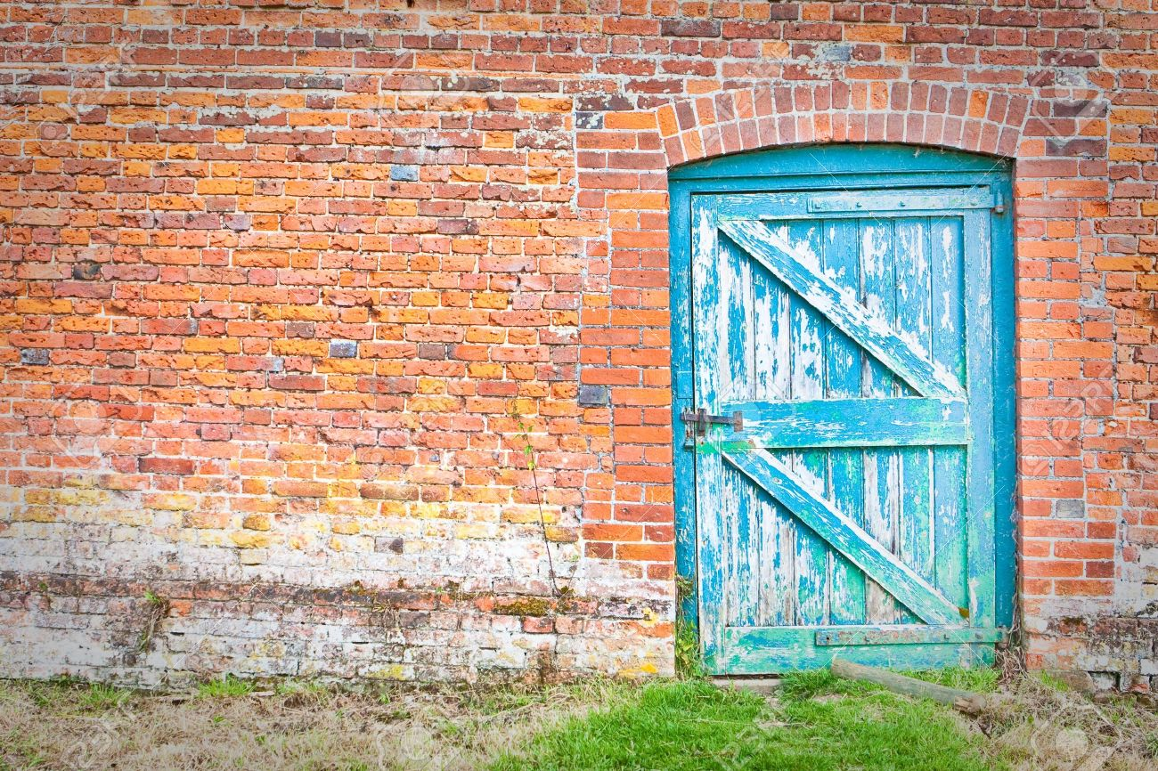 A quirky blue door set at an odd angle in a red brick wall in an English country garden Stock Photo - 10179896