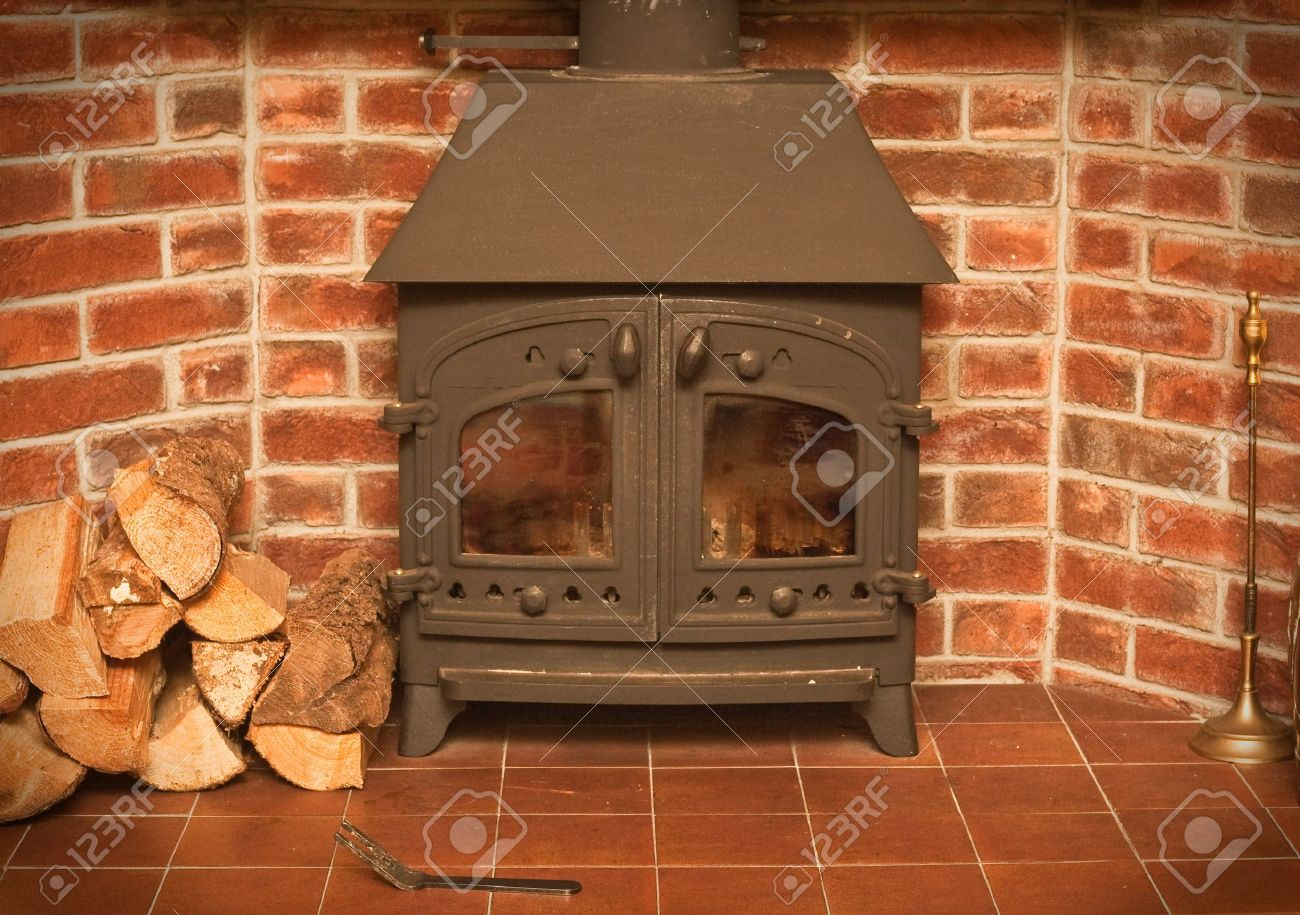 A wood burning stove in a red brick fireplace Stock Photo - 10179861