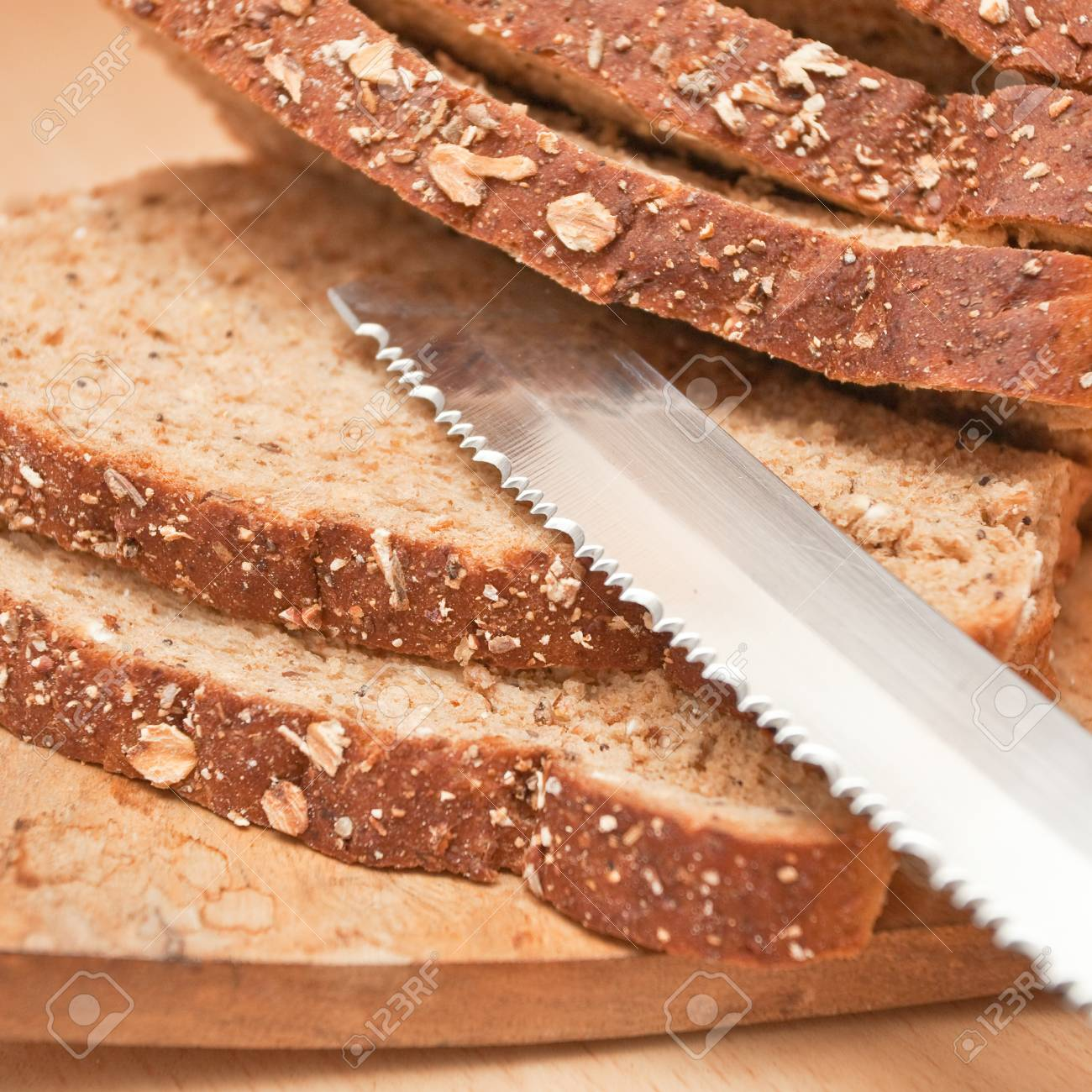 Sliced wholemeal bread and a bread knife on a wooden board Stock Photo - 11236241
