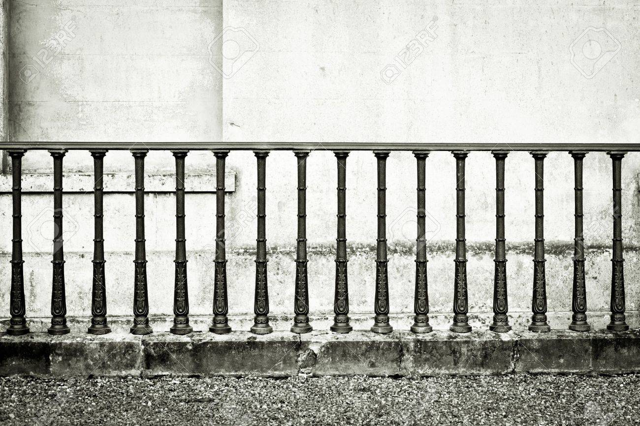 Monochrome image of wrought iron railings against a stone wall Stock Photo - 15636532