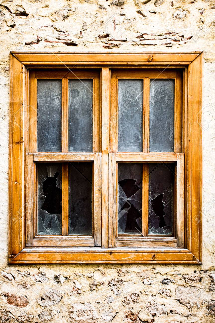 A Wooden Window Frame With Broken Glass