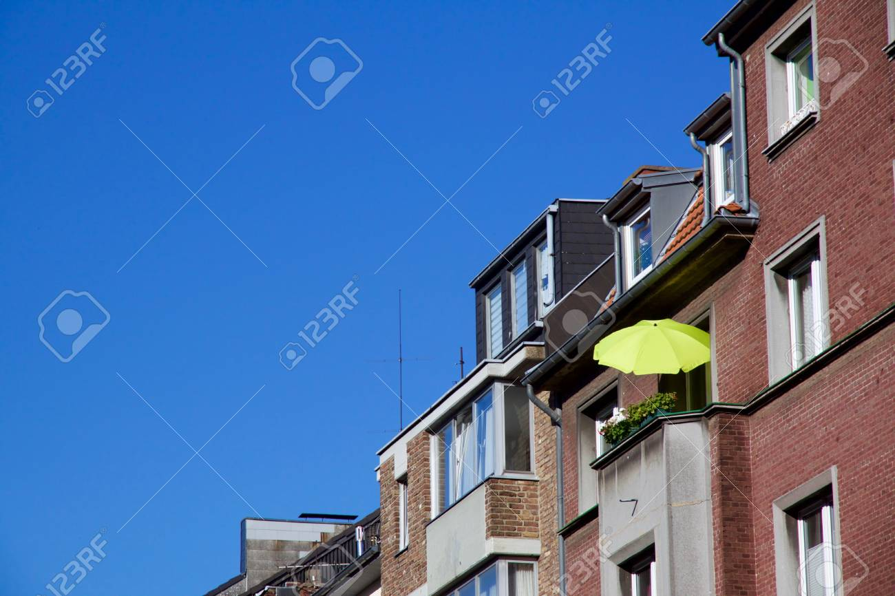 Row of houses, one with a sunshade on balcony for a relaxed evening,