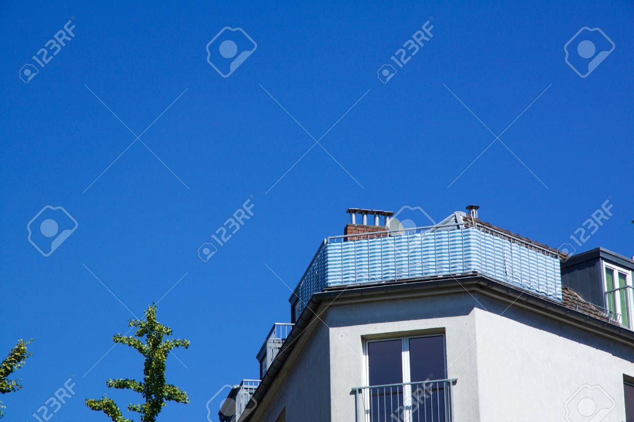Cornered roof terrace/balcony of apartment house with copyspace against a blue sky in Aachen, Germany - 78451775