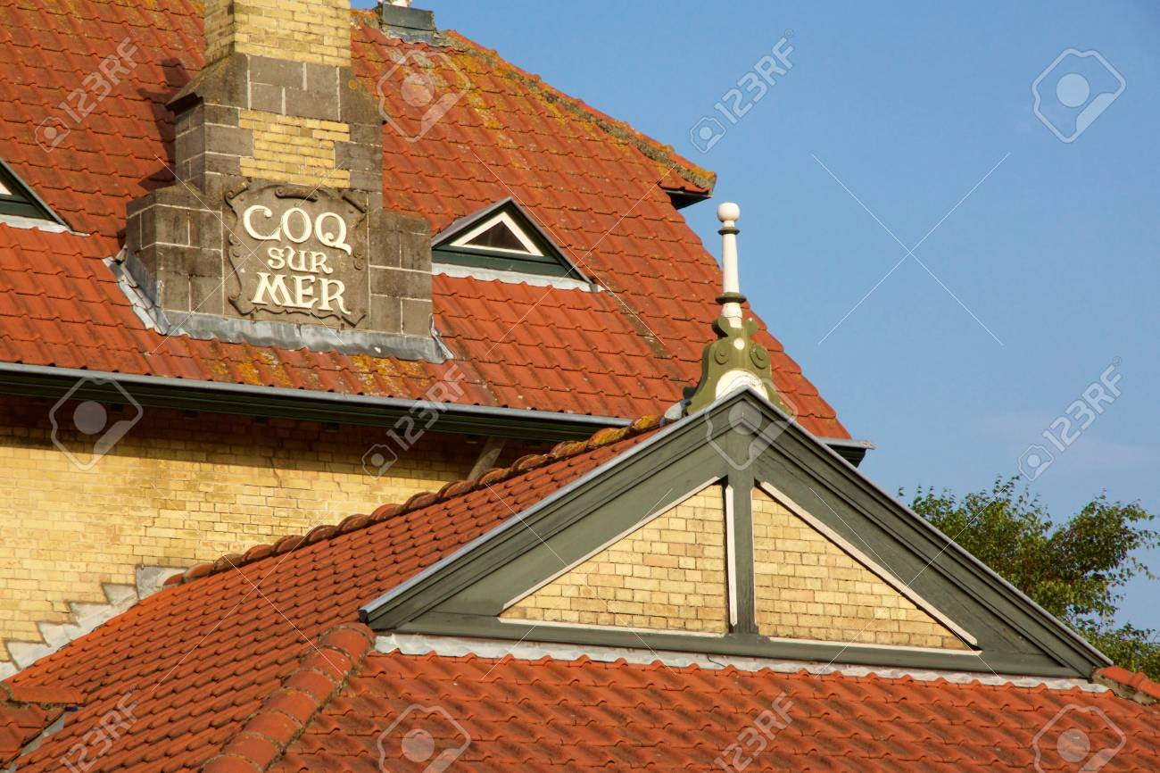Historical architecture in De Haan, Belgium in Belle Epoque style with an interesting red roofed townhouse against a blue sky - 78451776
