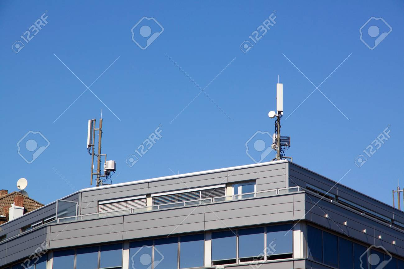 Exterior view of the upper floor and roof of a modern flat roof urban house with communication antennae on the rooftop against a blue sky - 78451770