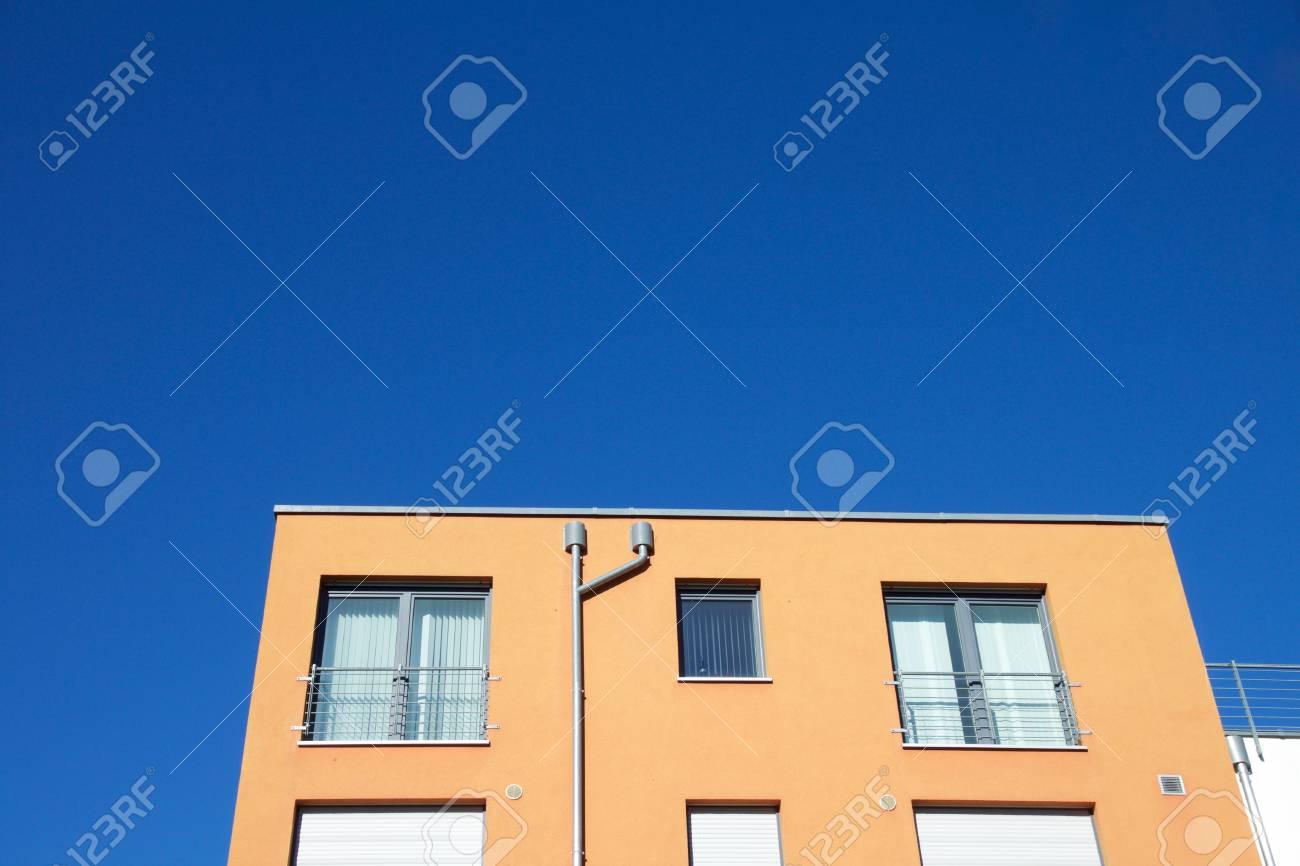 Closeup of an orange apartment building against a blue sky - 78451780