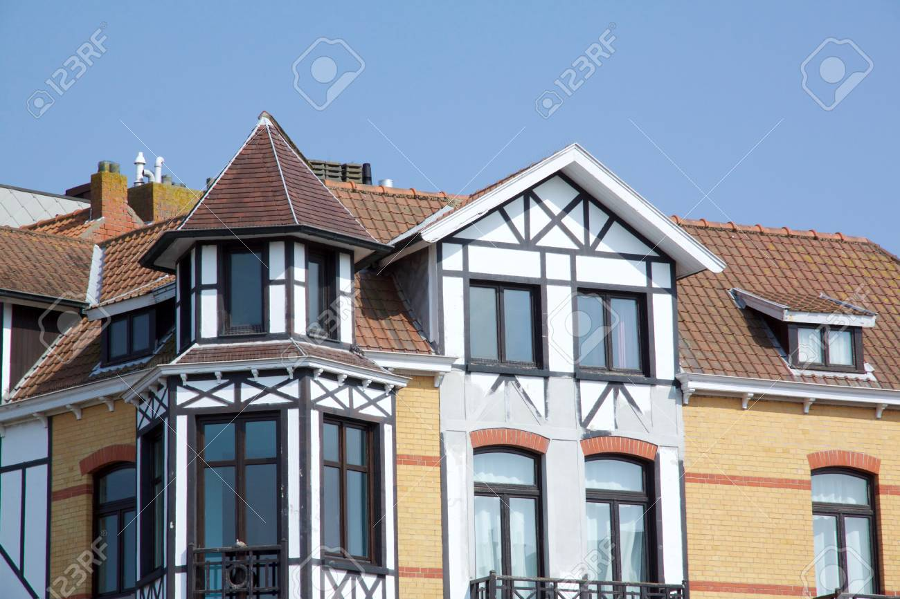 Historical architecture in De Haan, Belgium in Belle Epoque style with an interesting dark roofed townhouse against a blue sky - 78584532