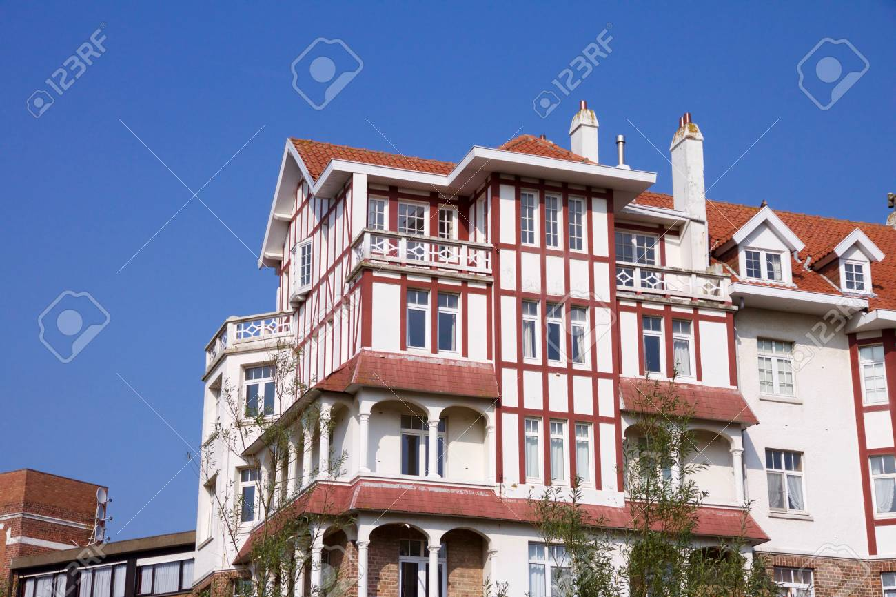 Historical architecture in De Haan, Belgium in Belle Epoque style with an interesting red roofed townhouse against a blue sky - 79149719