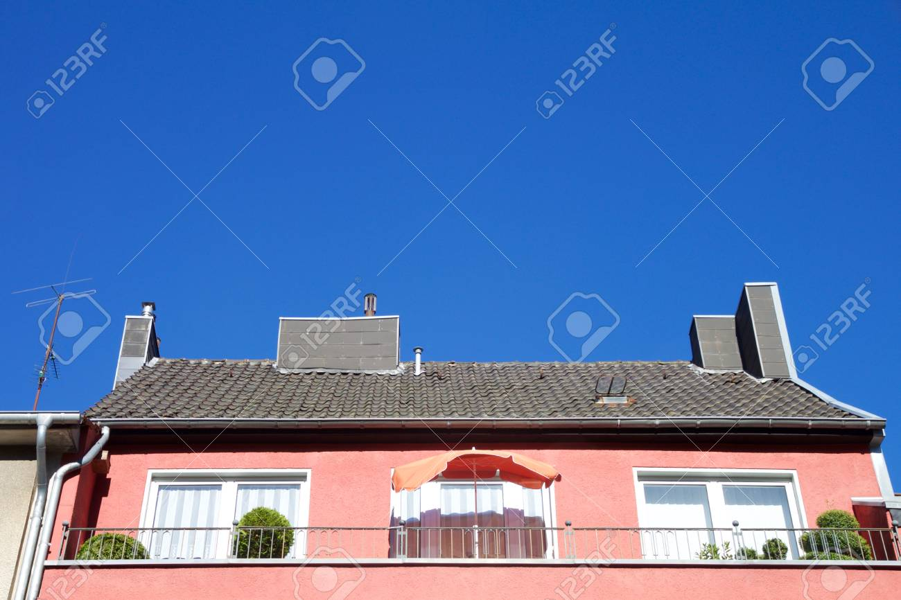 Red house with sunshade on balcony and chimney on roof against