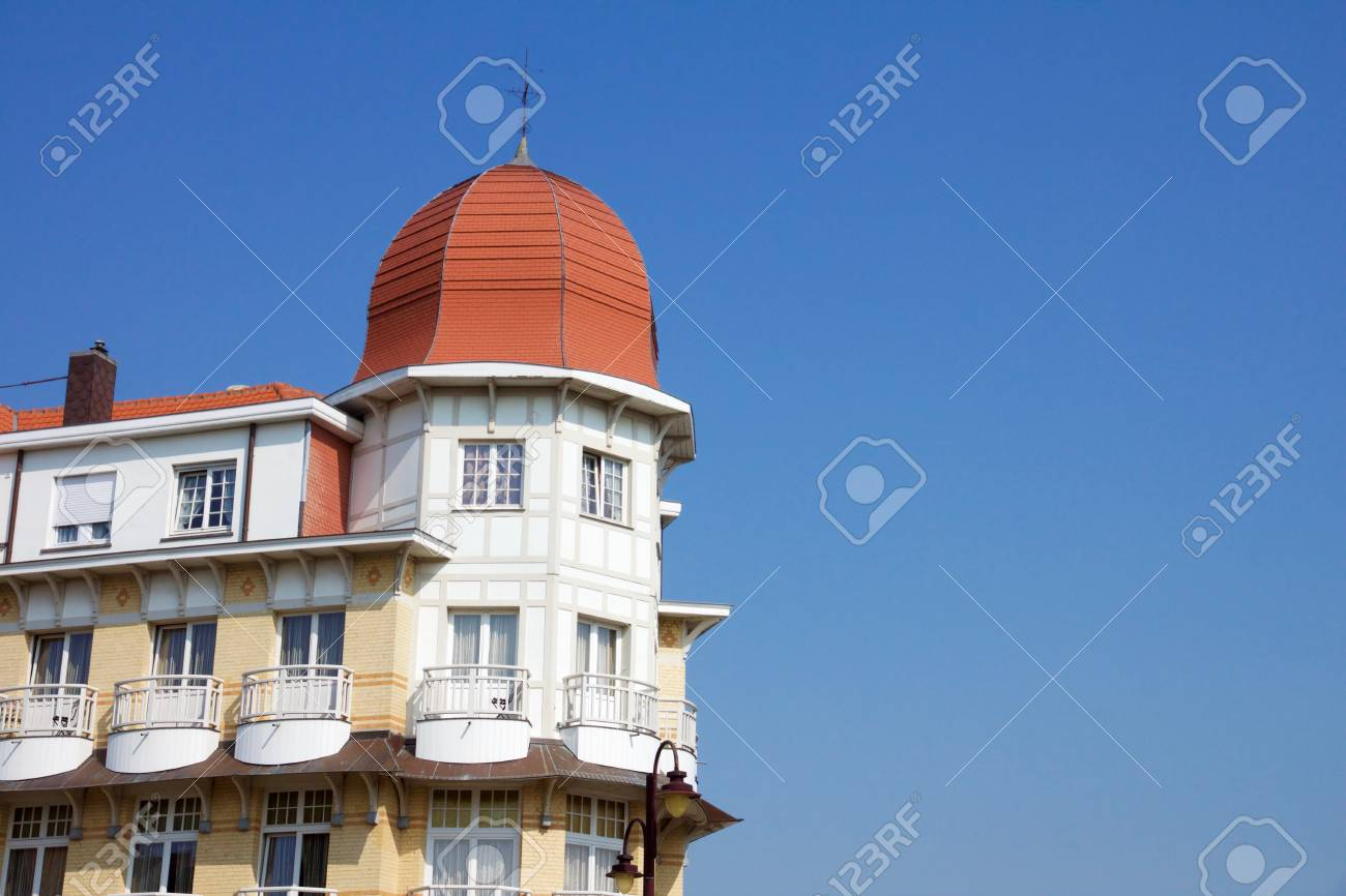 Historical architecture in De Haan, Belgium in Belle Epoque style with an interesting red roofed townhouse with corner octagonal turrets and wrought iron balconies against a blue sky - 78728747