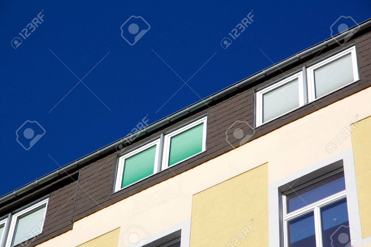 Facade of a yellow house with windows with closed shutters in different colors. Against a blue sky with copyspace. Aachen, Germany - 78753702