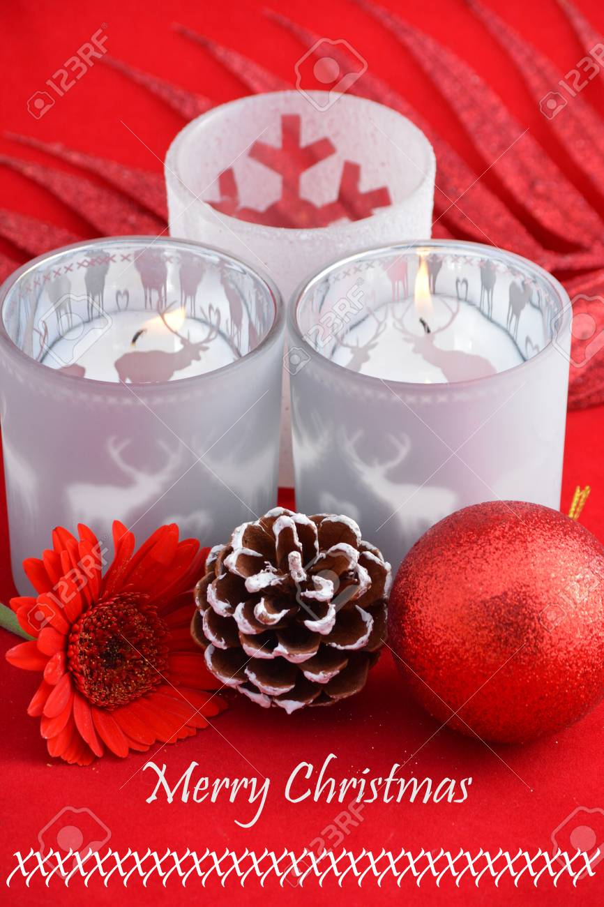 christmas background with three red tea candle holders decorated with a gerber daisy pine apple and