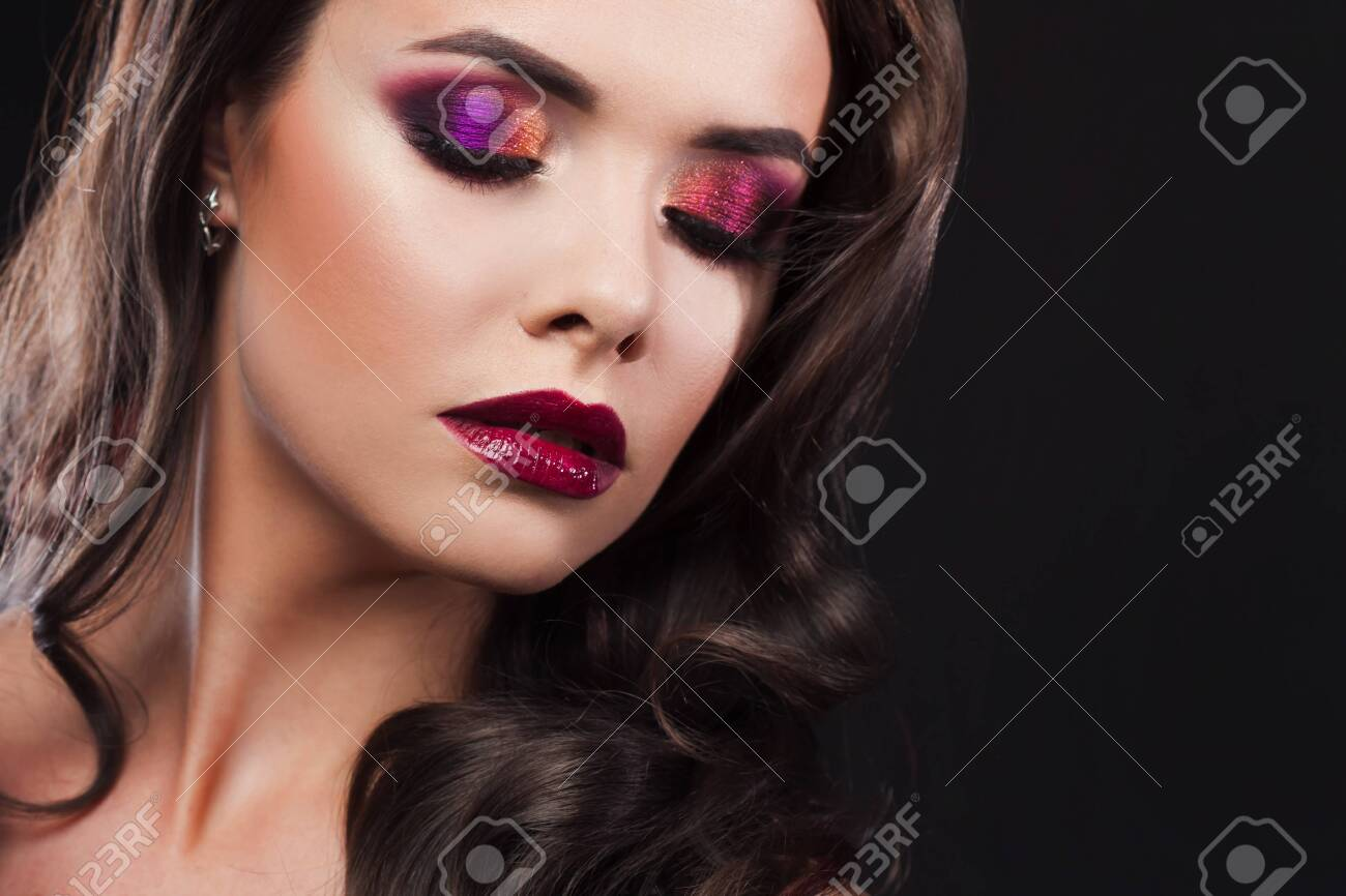 Gorgeous young brunette in a chic evening look. Scarlet lips and eye shadow, wave hair styling - 145577860