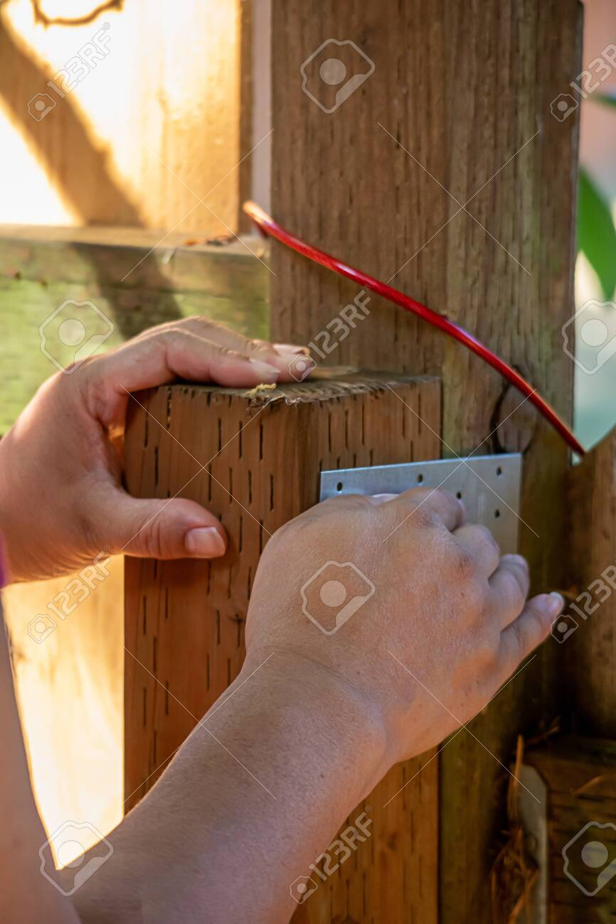 Picture of: Woman S Hand Holding Fence Post With Support Bracket In Metal Stock Photo Picture And Royalty Free Image Image 135771063