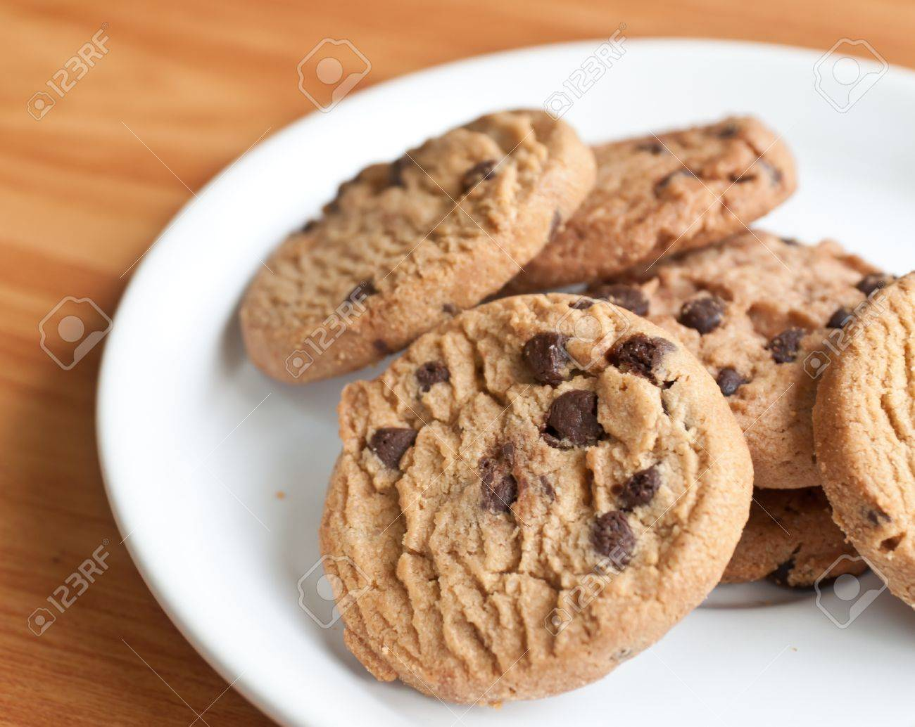 chocolate chips cookies in a dish on the wood teble. - 13354136