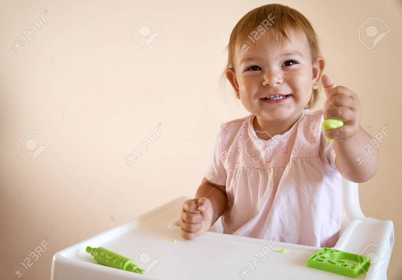 Little child engaged in playdough modeling at table, copy space. lifestyle - 128256334