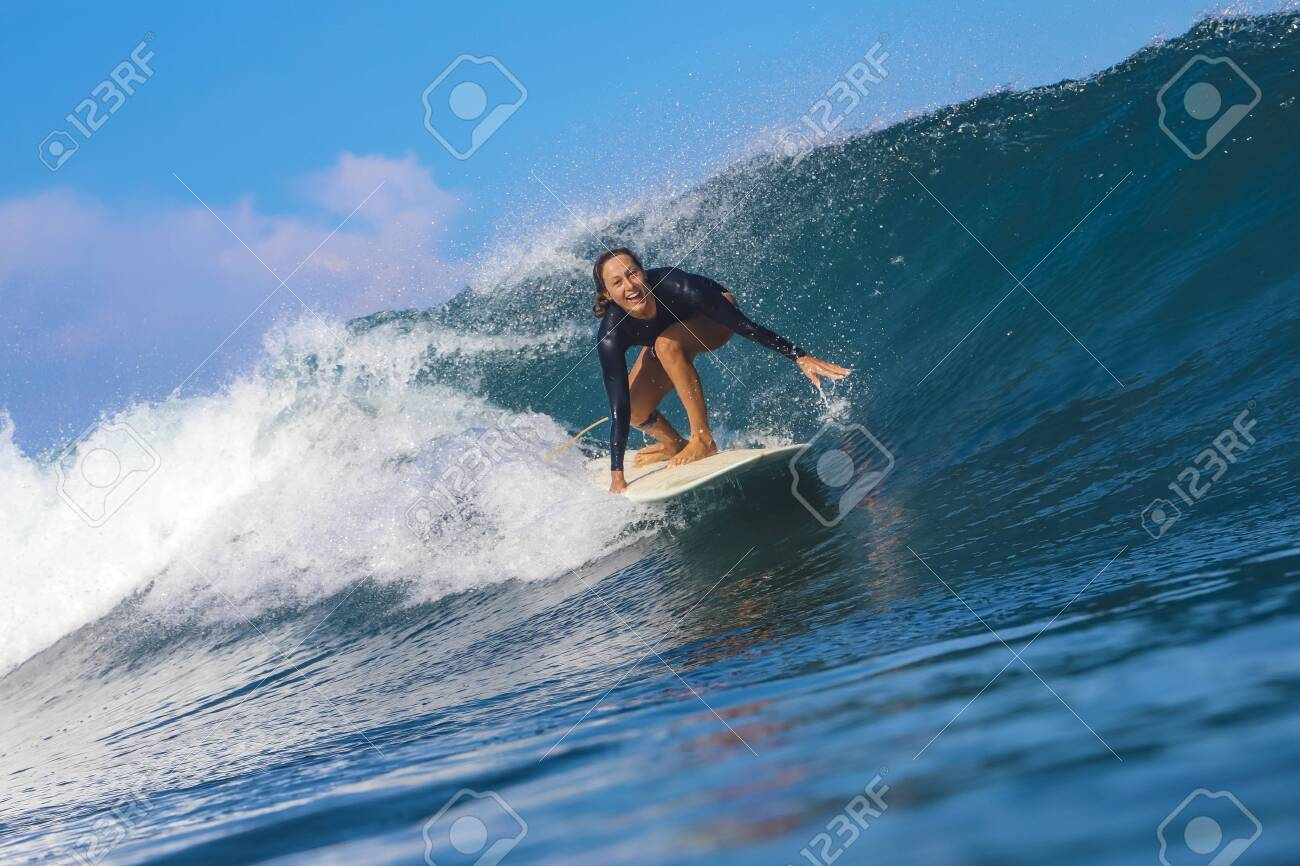 Female surfer on a blue wave at sunny day - 142664846