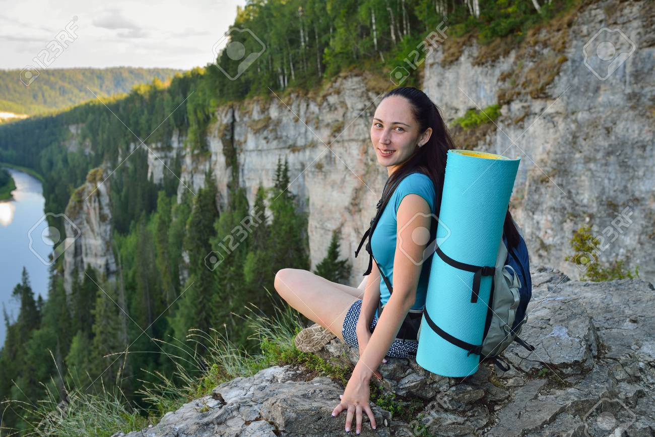 fbe4d5e9959 Stock Photo - Young woman with backpack sitting on cliff s edge at high  mountain and looking at camera.