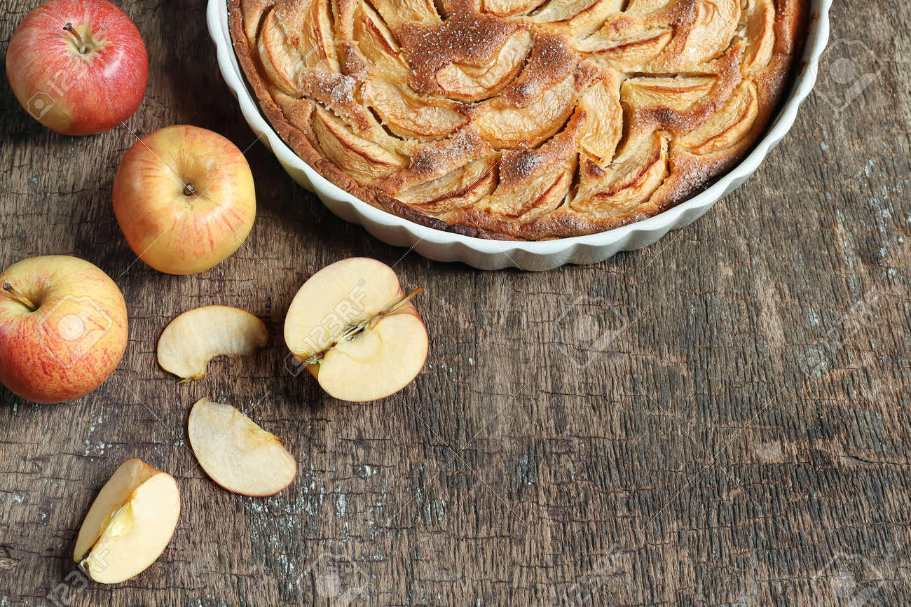 Traditional french homemade apple pie in a white ceramic baking form and autumn apples on old dark wooden background. Top view, copy space - 156303106