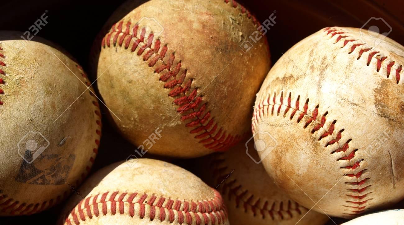 old baseballs in a bucket after a long season