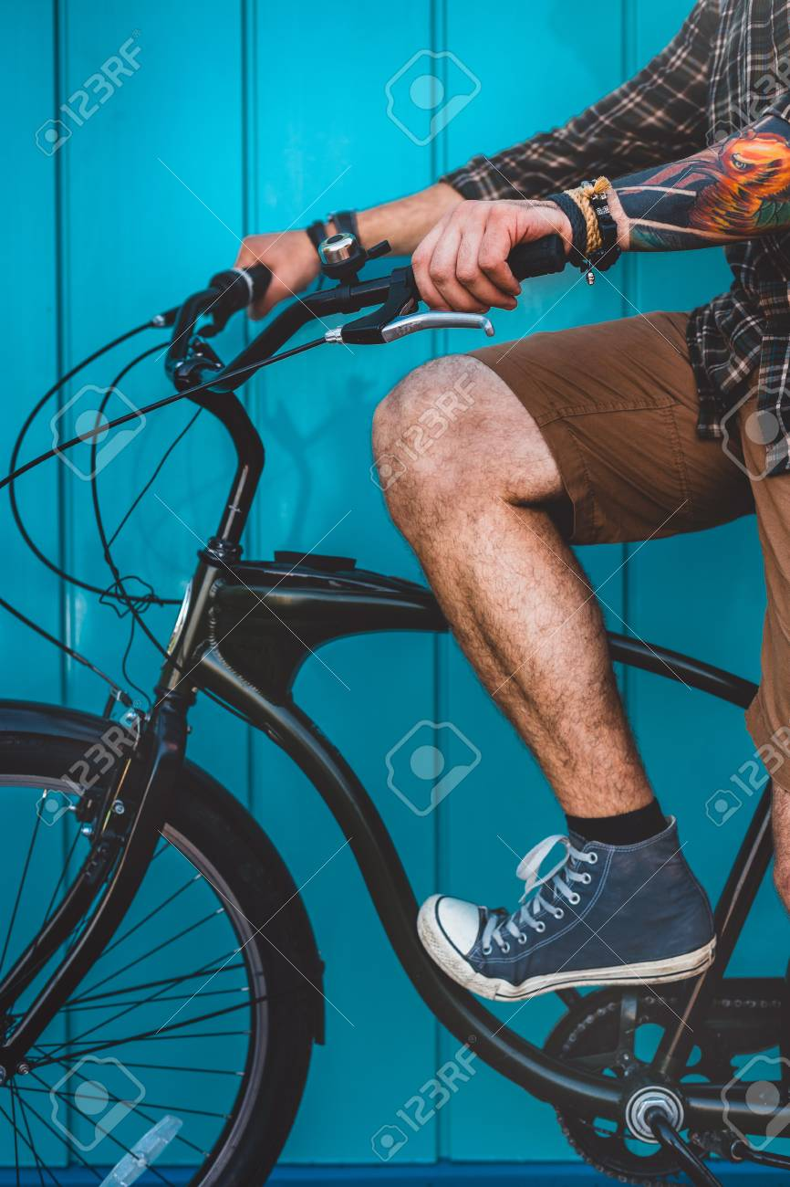 Unrecognizable Adult Man Sitting On A Bicycle Along A Blue Wall Background Daily Lifestyle Urban Resting Concept Standard-Bild - 82331703