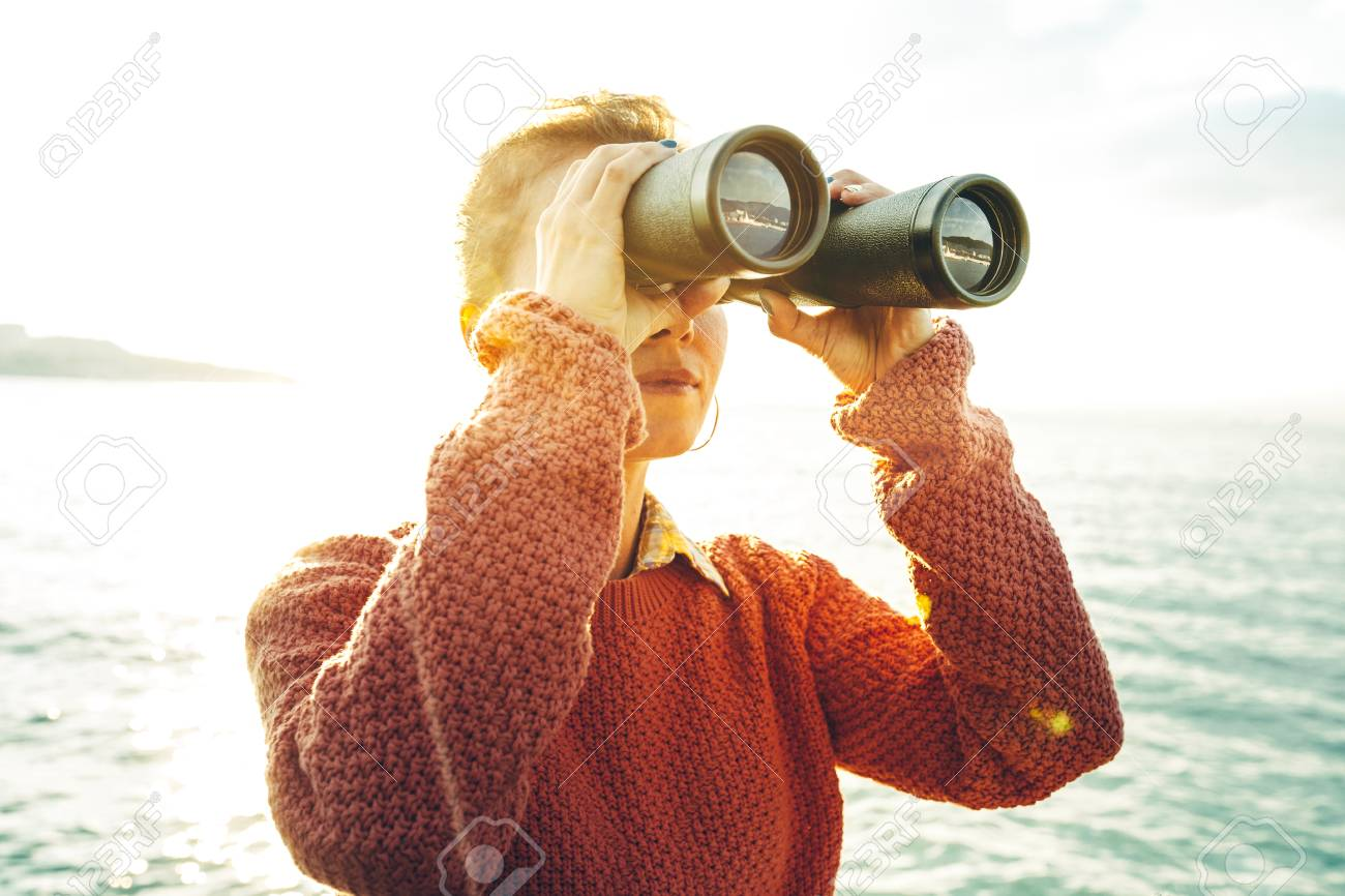 Beautiful Young Girl Looking Through Binoculars At The Sea On A Bright Sunny Day. Wanderlust Journey Concept - 93279741