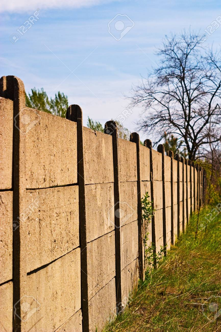 Old concrete boundary fence with nails on sunny day Stock Photo - 6937726