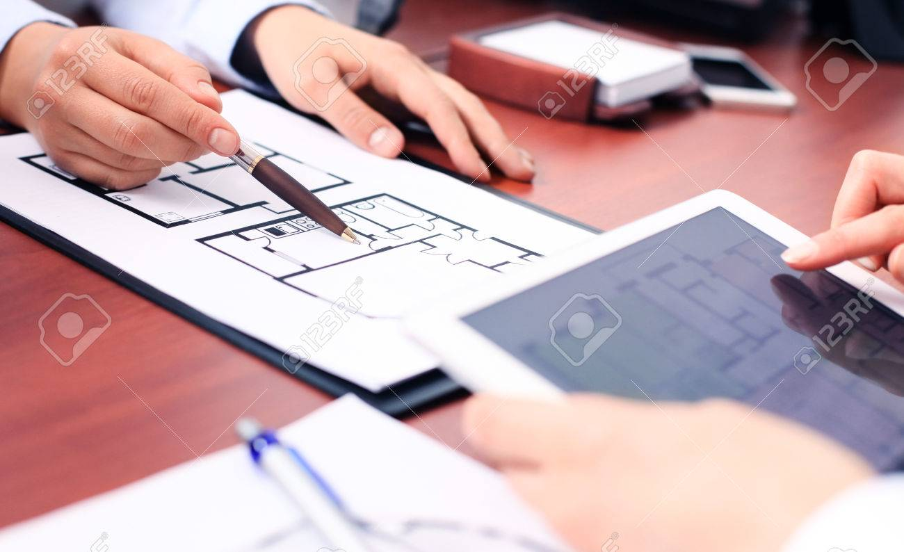 Real-estate agent showing house plans on electronic tablet - 36503650