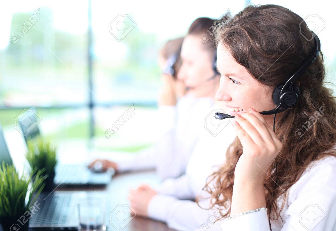 Portrait of smiling female customer service agent wearing headset with colleagues working in background at office - 40833294