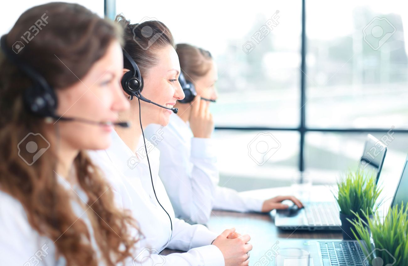 portrait of smiling female customer service agent wearing headset portrait of smiling female customer service agent wearing headset colleagues working in background at office