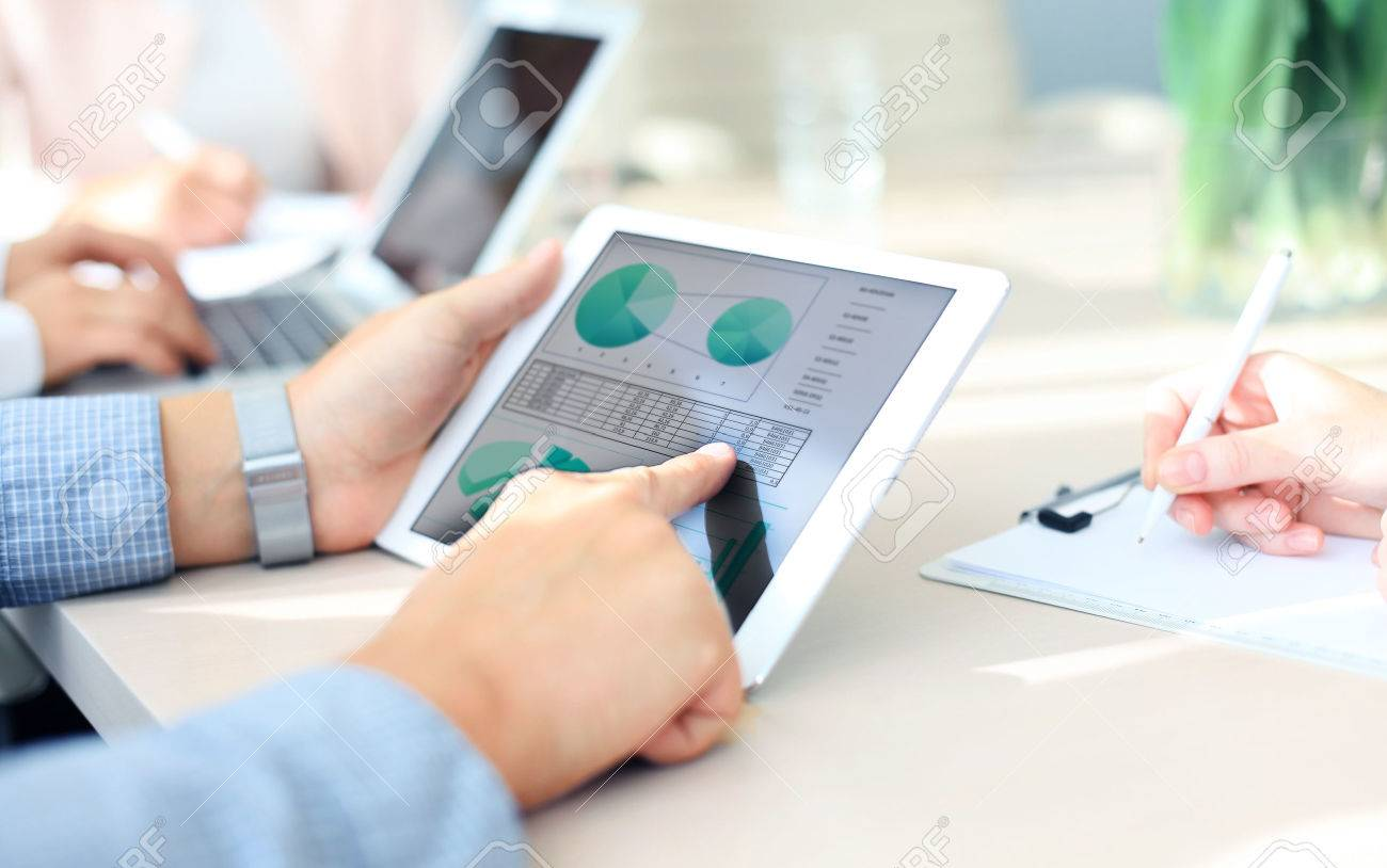Business person analyzing financial statistics displayed on the tablet screen - 45261590