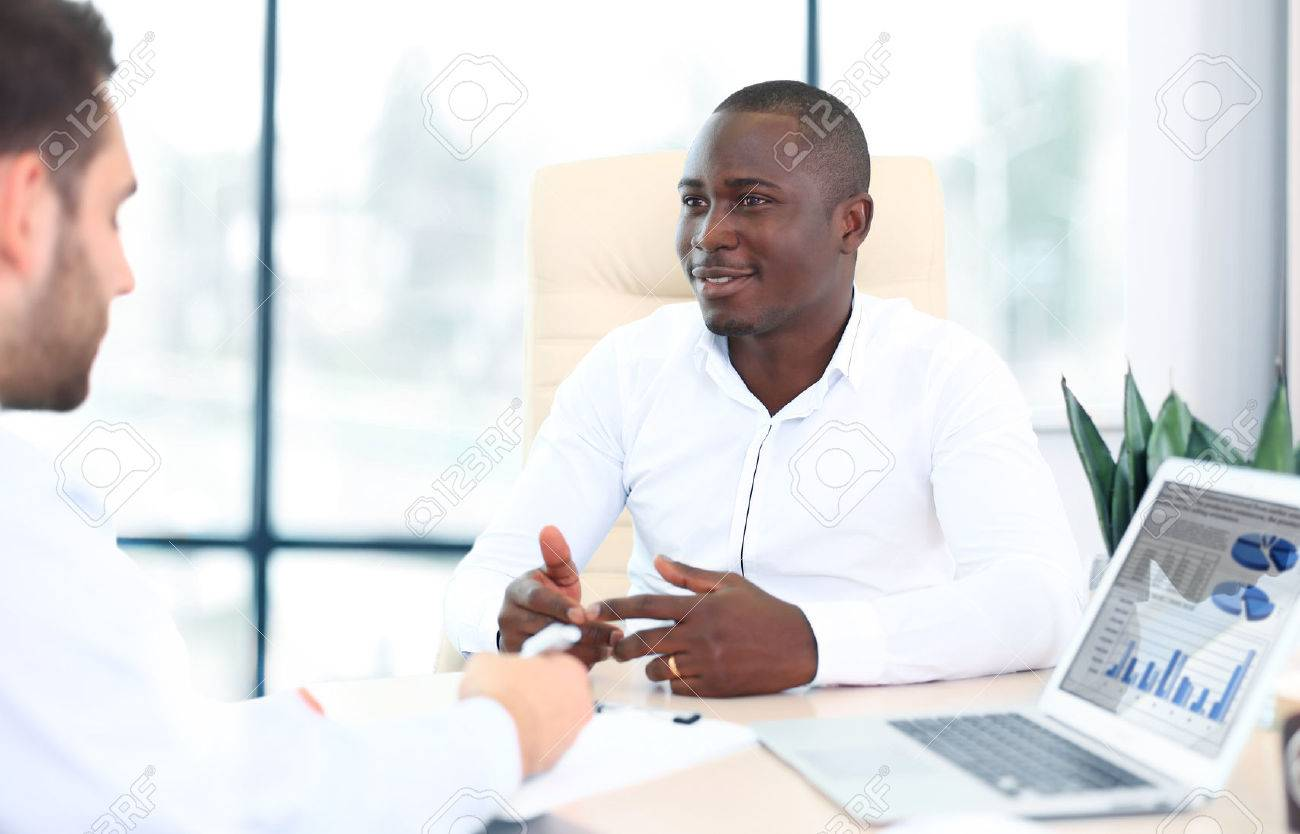 Image of two young businessmen interacting at meeting in office - 48969015