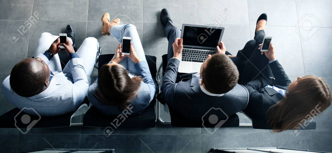 Group of attractive young bussinespeople sitting on the chairs using a laptop, Tablet PC, smart phones, smiling - 62834398